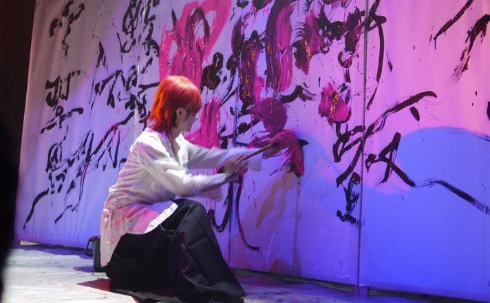 大きな筆で虫雲とピンクの文字で書いている